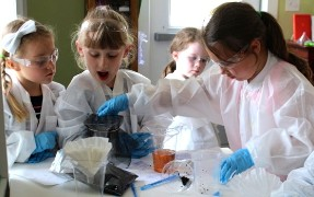 Elementary students are wearing lab coats and filtering water.