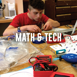 A student testing a circuit board during robotics.