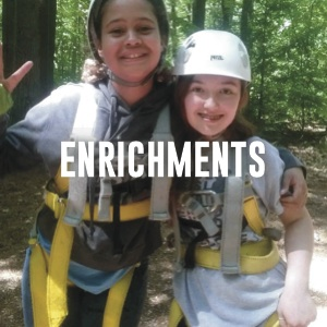 enrichments: students wearing harnesses in a ropes course