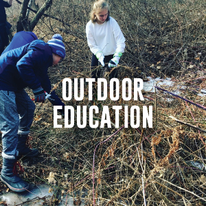 outdoor education: students clearing brush by the river