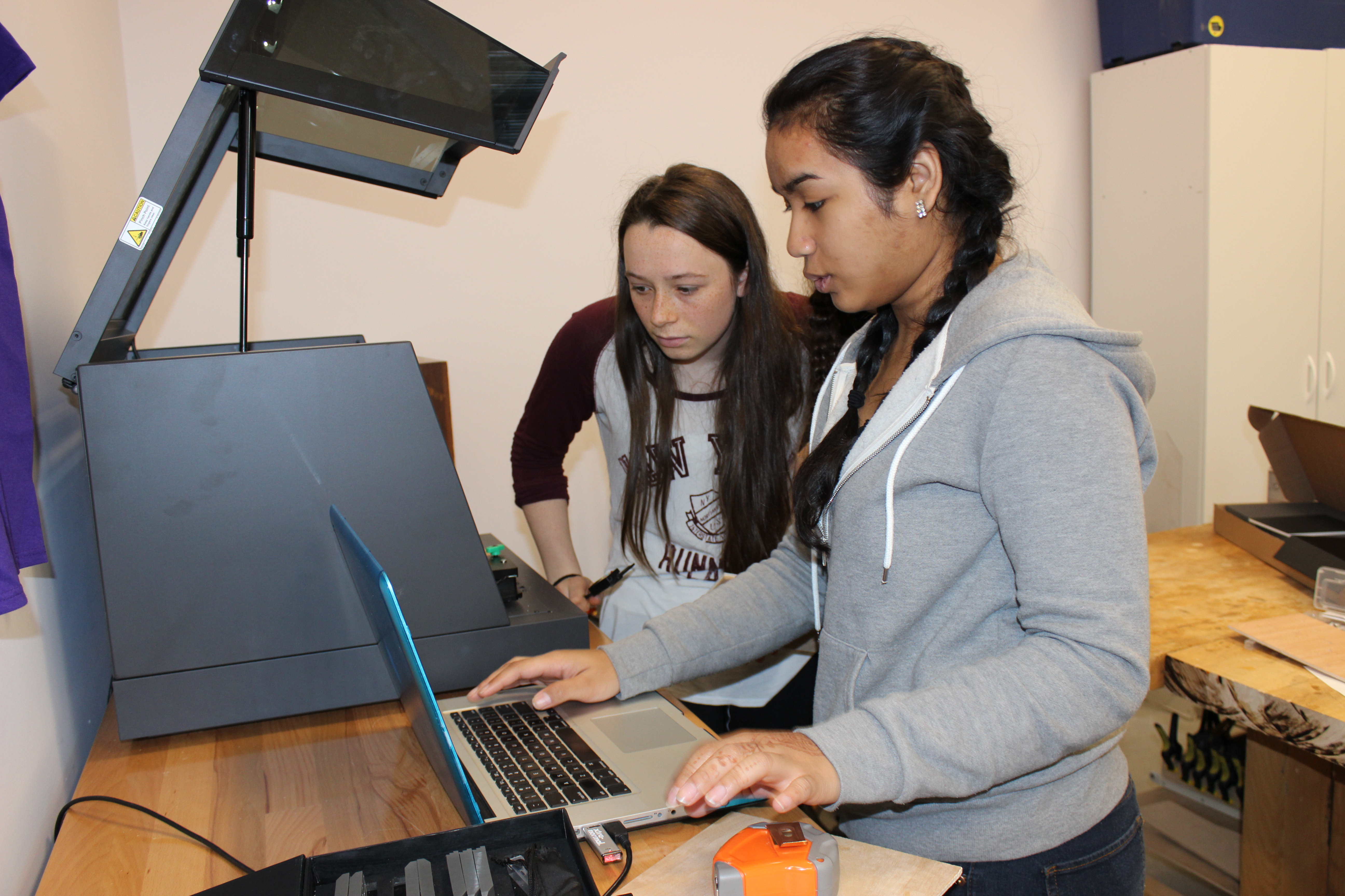 Two female students using a computer to print from the Carvey.