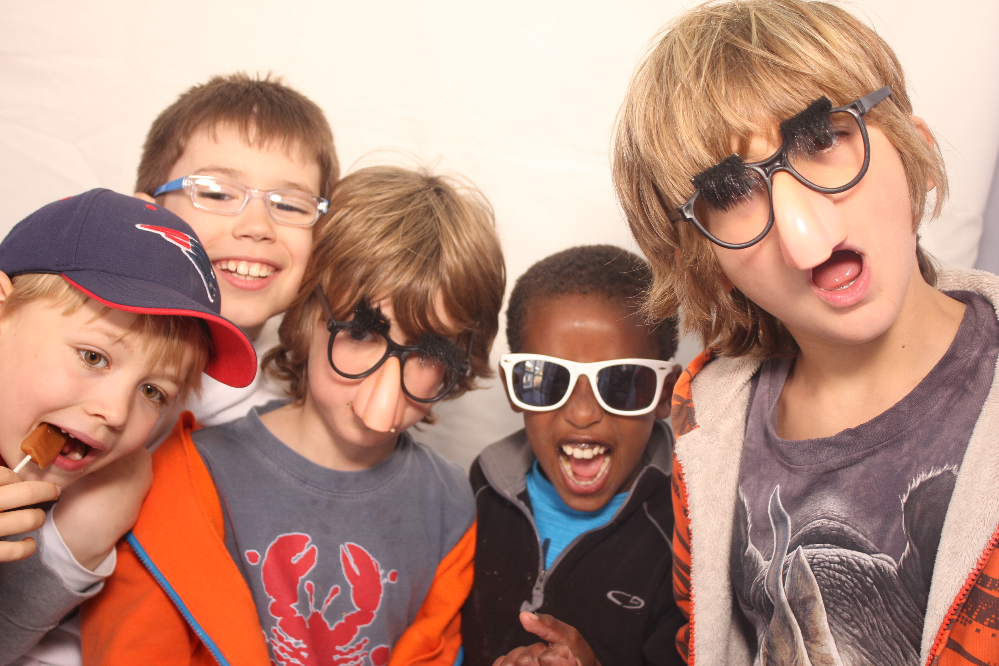 Sparhawk students wearing glasses and smiling in a photo booth.